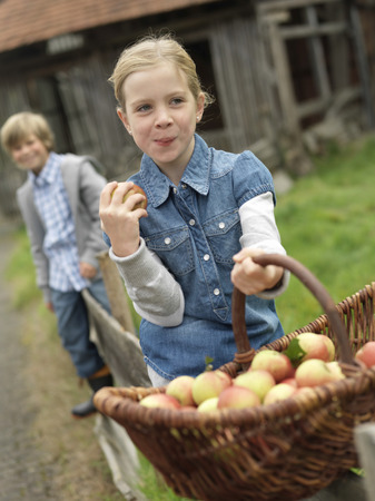 Girl with apple basket eating apples LANG_EVOIMAGES