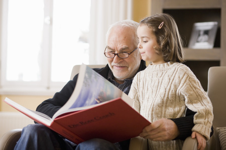 old man reading book to young girl LANG_EVOIMAGES