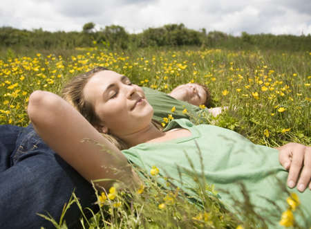 arms behind head: Couple Sleeping in Meadow LANG_EVOIMAGES