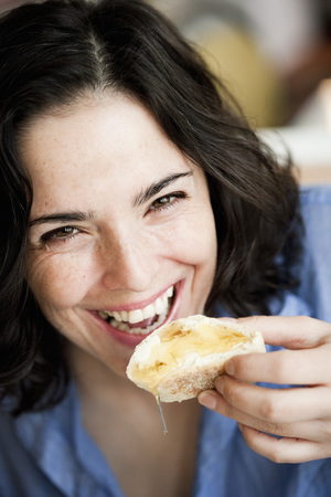 savour: Woman Eating Bread With Honey LANG_EVOIMAGES