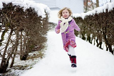 Scandinavian girl running in snow LANG_EVOIMAGES