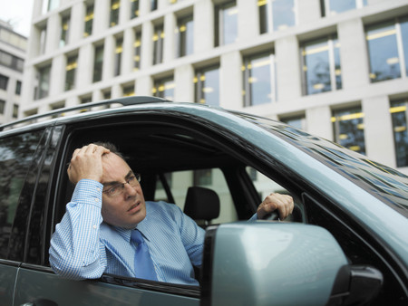 hardships: Frustrated businessman in car