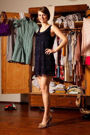 messy clothes: Woman in a dress in front of cupboard LANG_EVOIMAGES