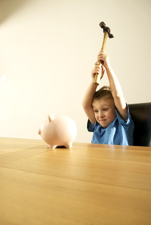 boy smashing piggy bank