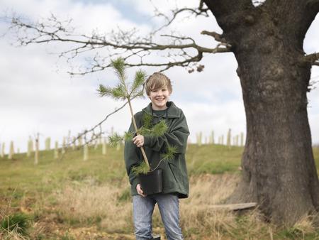 replenishing: Boy Holding Young Tree
