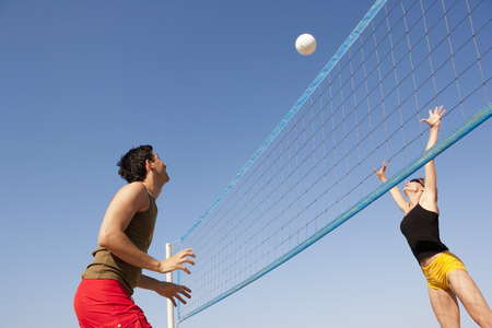 Couple Playing Beach Volleyball LANG_EVOIMAGES