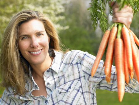 arms lifted up: Woman holding a carrot bunch