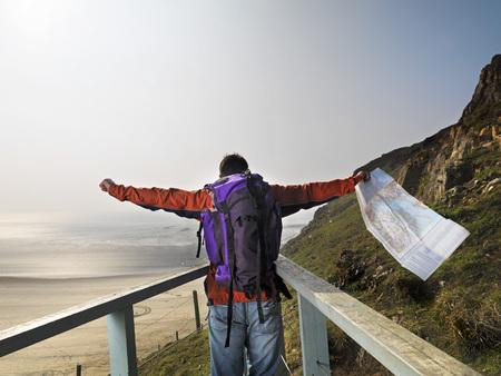 accomplishes: man hiking on cliff edge