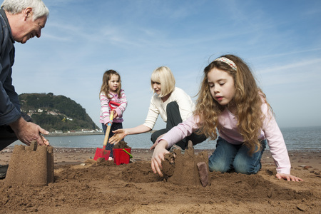 knelt: mature couple with children on beach LANG_EVOIMAGES