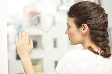 indecisive: Woman looking sadly at a painted heart.