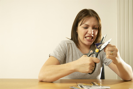 woman cutting credit cards LANG_EVOIMAGES