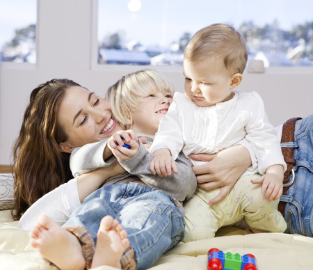 cuddled: Mother and children cuddling and playing