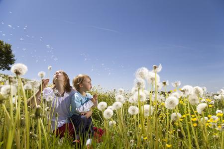 new age: Girl, boy blowing dandelions
