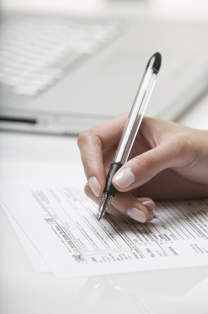 indebted: Woman filling out a tax form LANG_EVOIMAGES