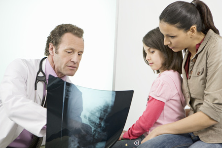 diagnoses: A male doctor showing patients an x-ray LANG_EVOIMAGES