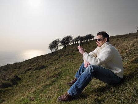conferring: man on phone on coastal hill