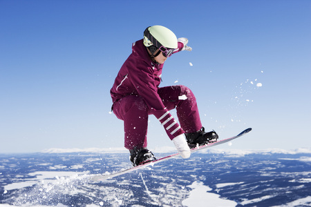 feats: Girl in jumpsuit grabbing board mid-air.