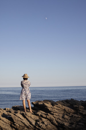 Girl standing on rocks by the sea LANG_EVOIMAGES
