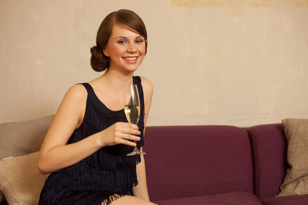 stylishly: Young woman holding glass of champagne
