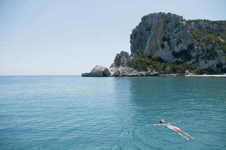 Woman Swimming in blue, rocky bay LANG_EVOIMAGES