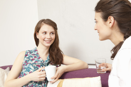 easygoing: Two women on a sofa, chatting.