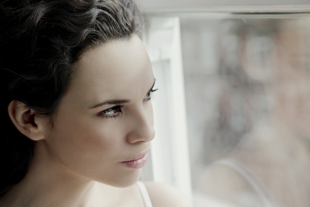 Woman looking through window. LANG_EVOIMAGES