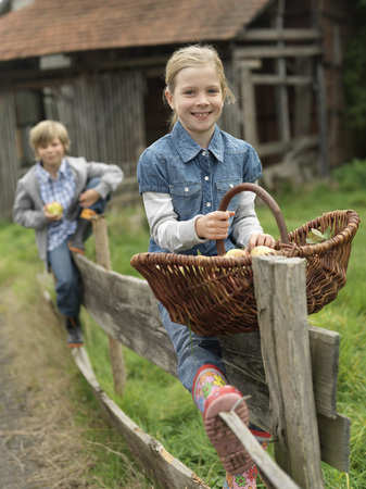 Girl and boy on fence with apples LANG_EVOIMAGES