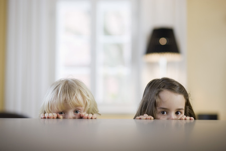 children looking over table edge