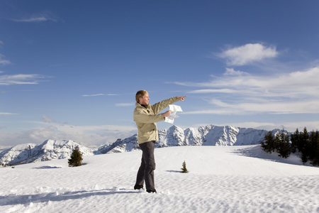 man in mountains pointing with map LANG_EVOIMAGES