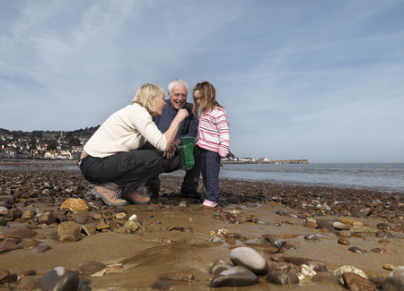 information age: mature couple with child on beach