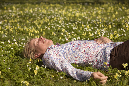 man lying in grass with spring flowers