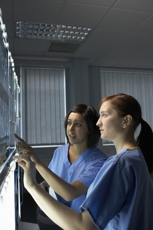 surgical gown: Two doctors looking at x-rays