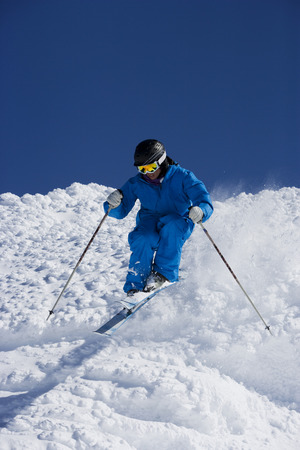 accomplishes: Man in blue skiing down hill.