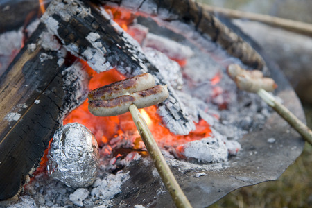 sausages roasting over barbecue fire