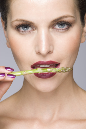 close up of female asparagus in mouth LANG_EVOIMAGES