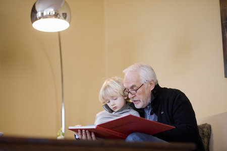grampa: old man reading book to young boy LANG_EVOIMAGES