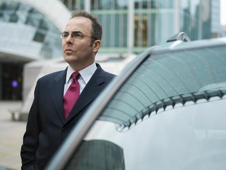 Businessman, chauffeur stood by car
