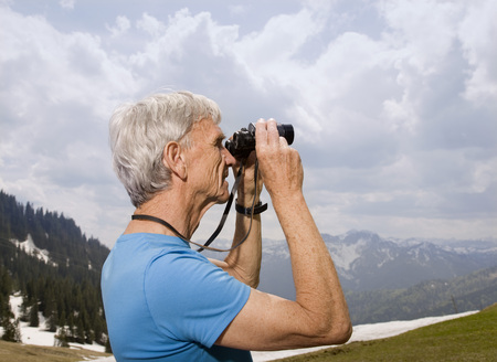 winter escape: senior man with binoculars in mountains