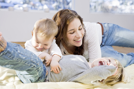 mischievious: Mother and children cuddling and playing