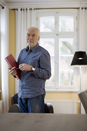living wisdom: old man with book looking at viewer