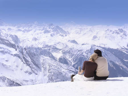 passions: couple sitting in the snow hugging LANG_EVOIMAGES