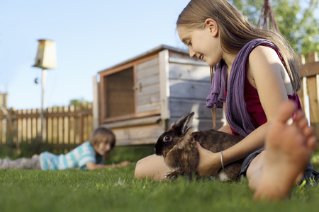 furs: Girl playing with rabbit in garden LANG_EVOIMAGES