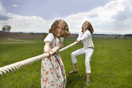Children pulling a rope in countryside LANG_EVOIMAGES