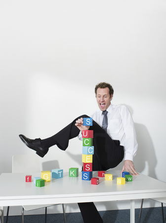 accomplishes: Business man puts last block on tower LANG_EVOIMAGES