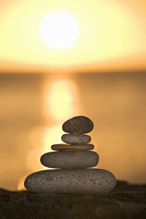 ascends: A stone stack against a setting sun