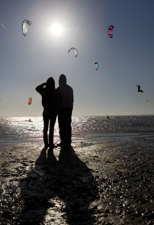 Couple watching kite boarders LANG_EVOIMAGES