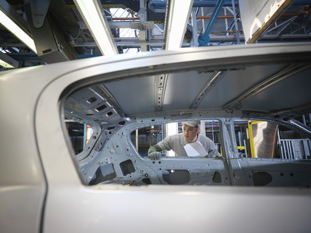 assembled: Car Plant Worker Inspecting Car