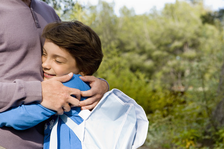 happy boy hugging dad back from school LANG_EVOIMAGES