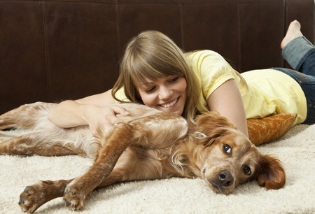 lays down: Young woman cuddling with her dog