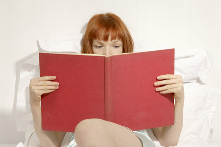 studied: woman reading book in bed